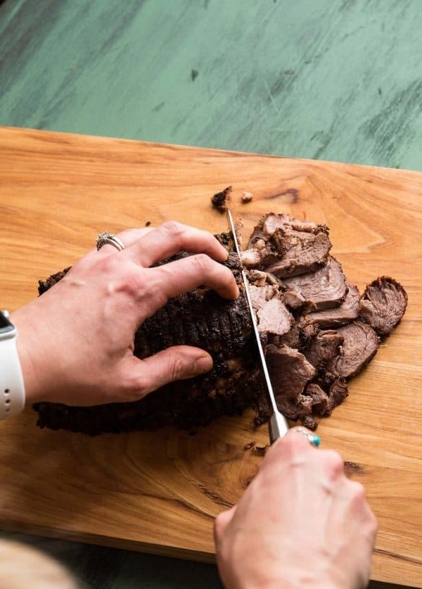 slicing lamb roast into thin pieces for gyros