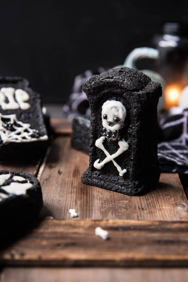 skull and crossbone tombstone cake on wooden surface