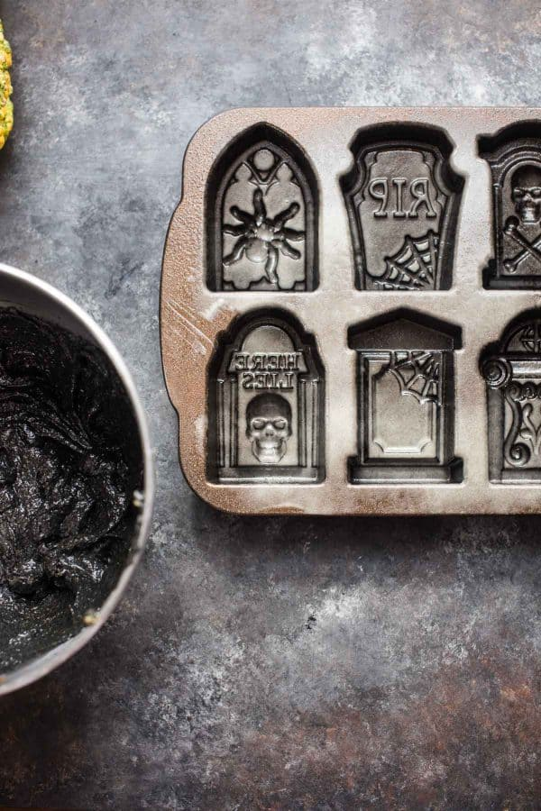 overhead photo of black cake batter and tombstone cake pan