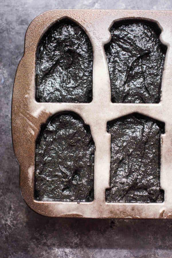 overhead view of black pumpkin cake batter in cakelet pan