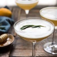 side angle of rosemary spring on top of a cocktail