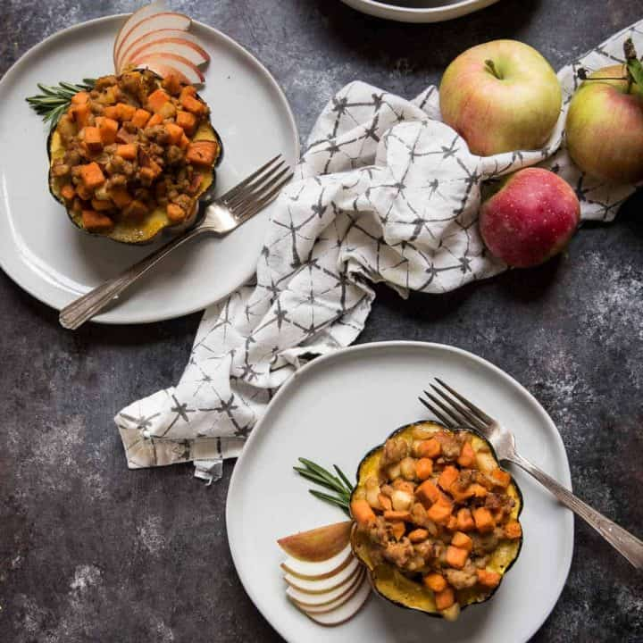 overhead angle of two stuffed acorn squash on plates with linen napkin and apples