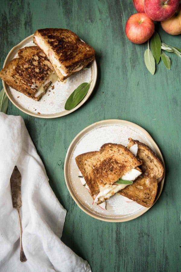 two grilled cheese sandwiches stacked on two plates with apples
