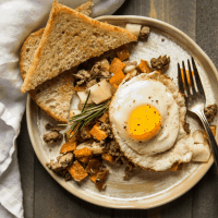 Fried egg over sweet potato hash with lamb and apples served with toast