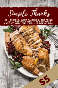sliced turkey on a platter with grapes and sage