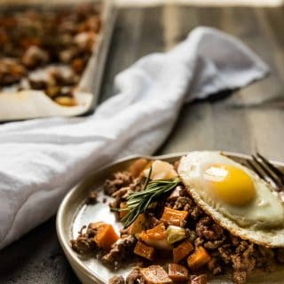 sweet potato hash with lamb and apples on a plate topped with a fried egg