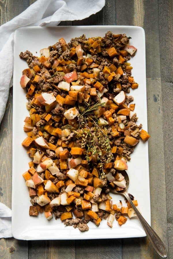 overhead angle of sweet potato hash on a serving platter with an antique spoon