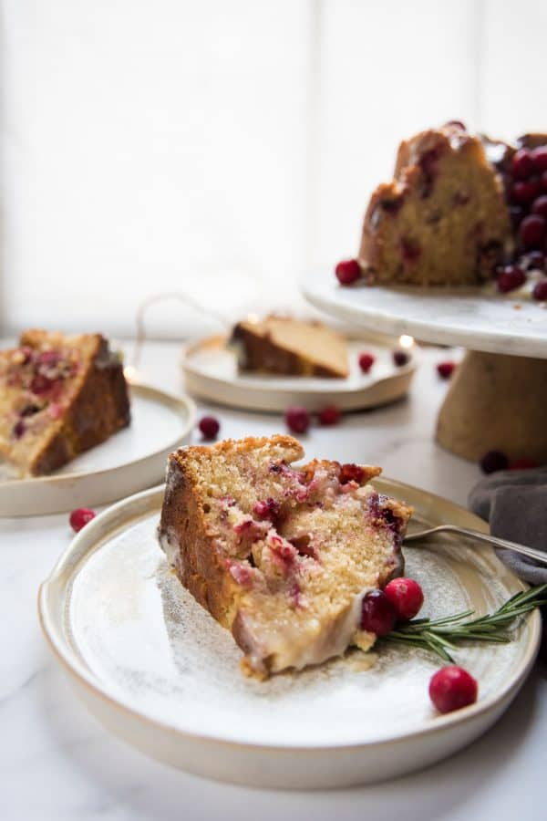 slices of tender cranberry cake on plates and cake stand