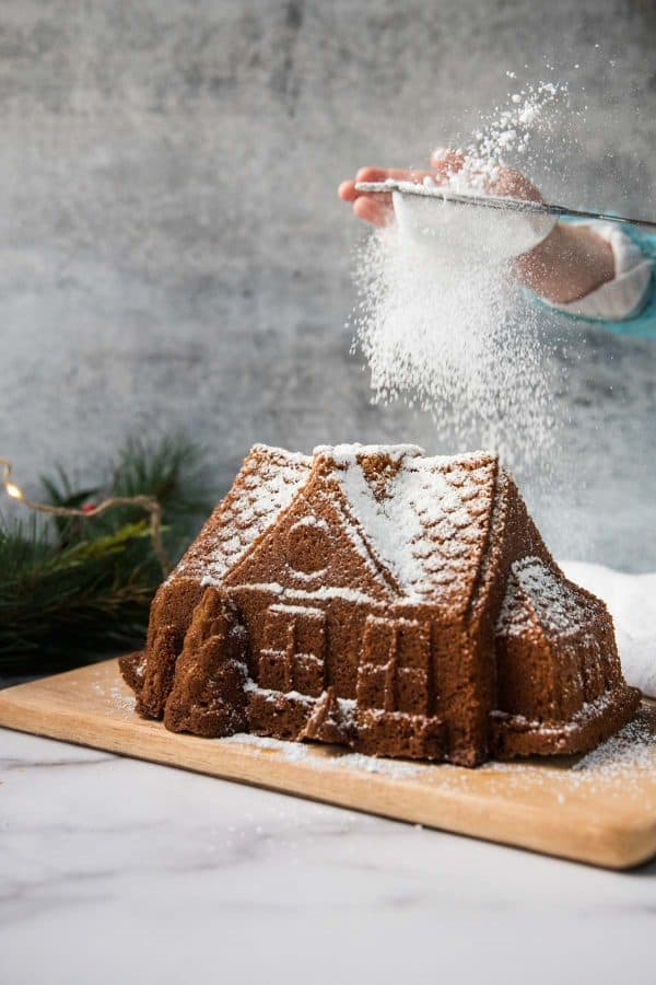 dusting confectioners sugar over gingerbread house