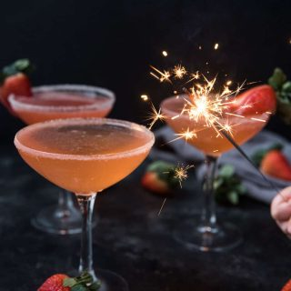 sparkler lighting up strawberry martinis