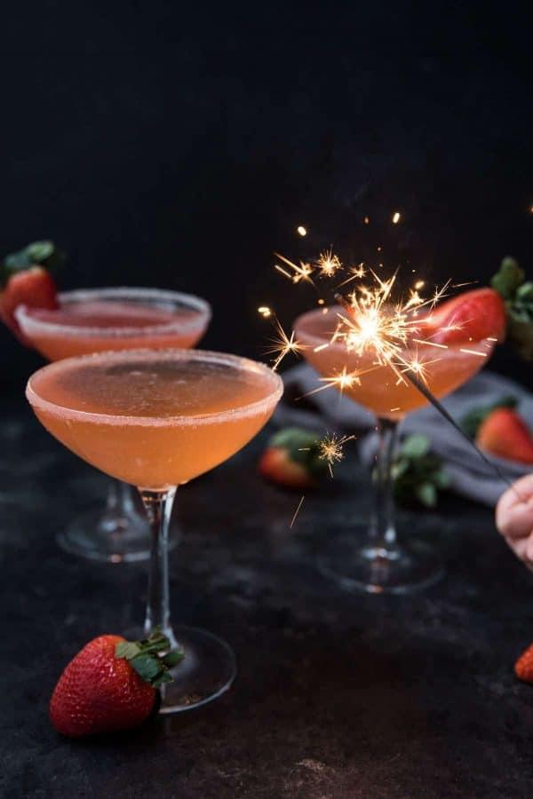 sparkler lighting up strawberry martinis