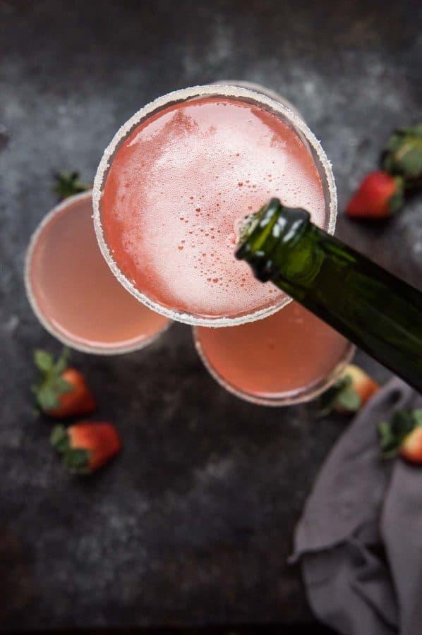 overhead of champagne pouring into a martini