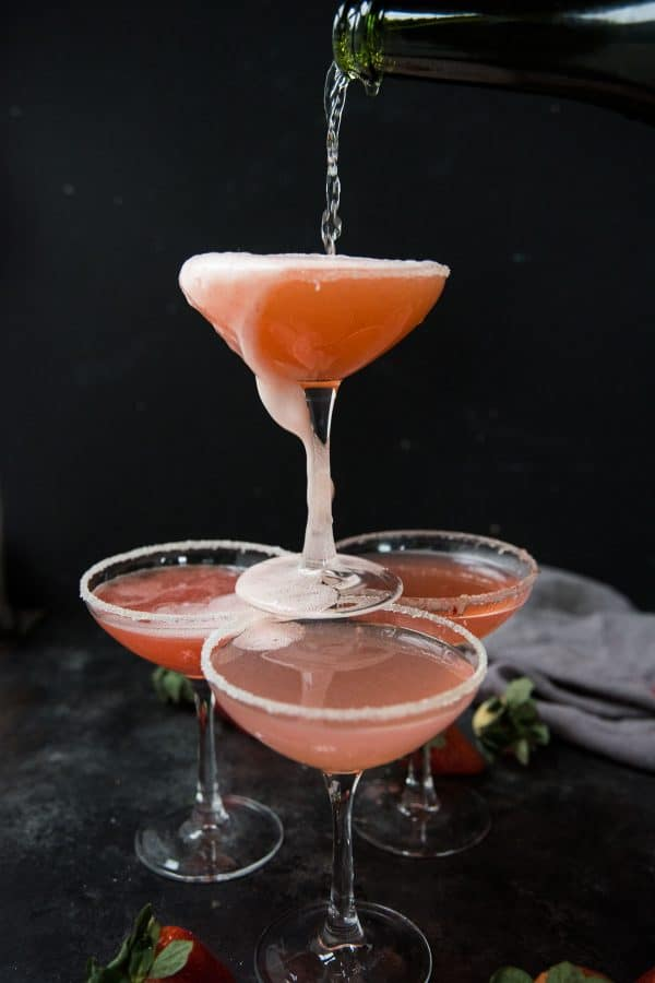 pouring champagne into stacked coupe glasses