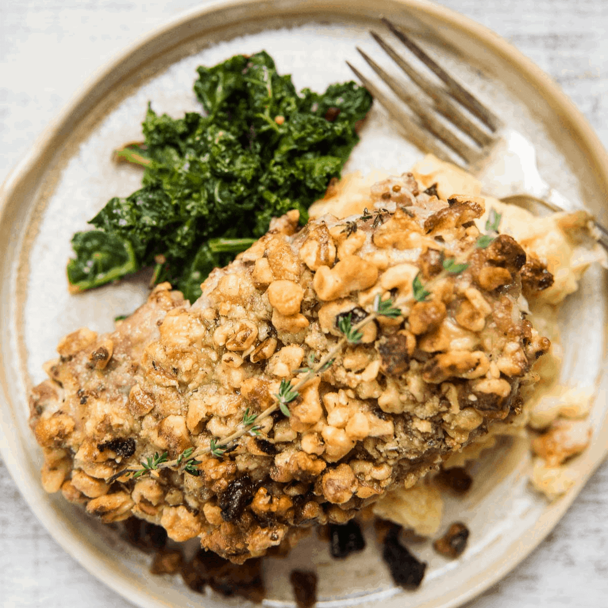 walnut crusted pork chop on a plate with kale and mashed potatoes