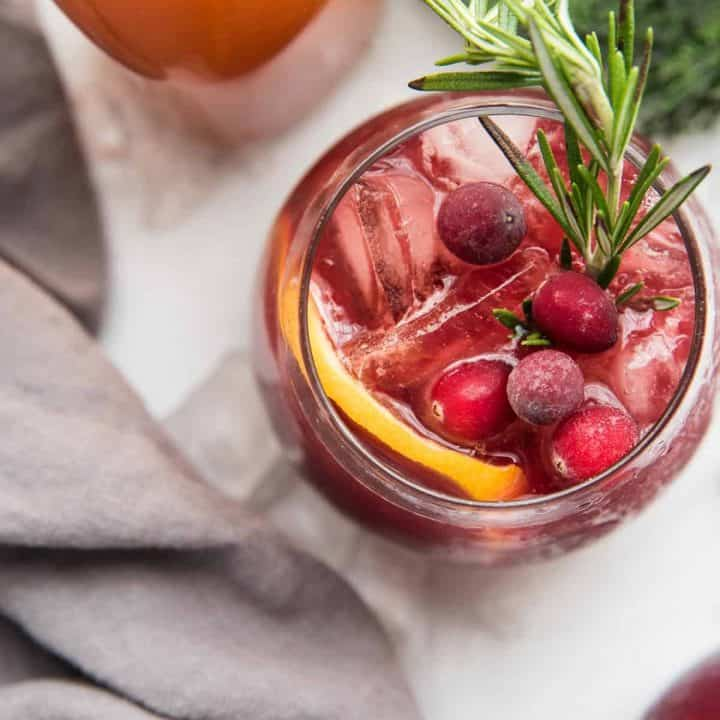 overhead angle of christmas sangria garnished with cranberries and rosemary