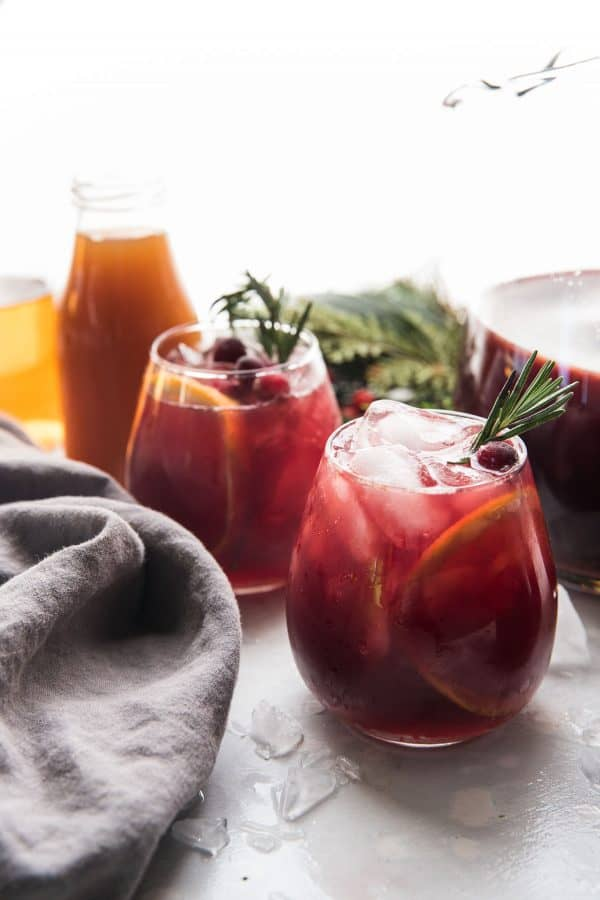 spiced christmas sangria poured into wine classes with sliced oranges and crushed ice