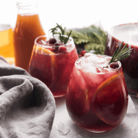 winter sangria poured into wine classes with sliced oranges and crushed ice
