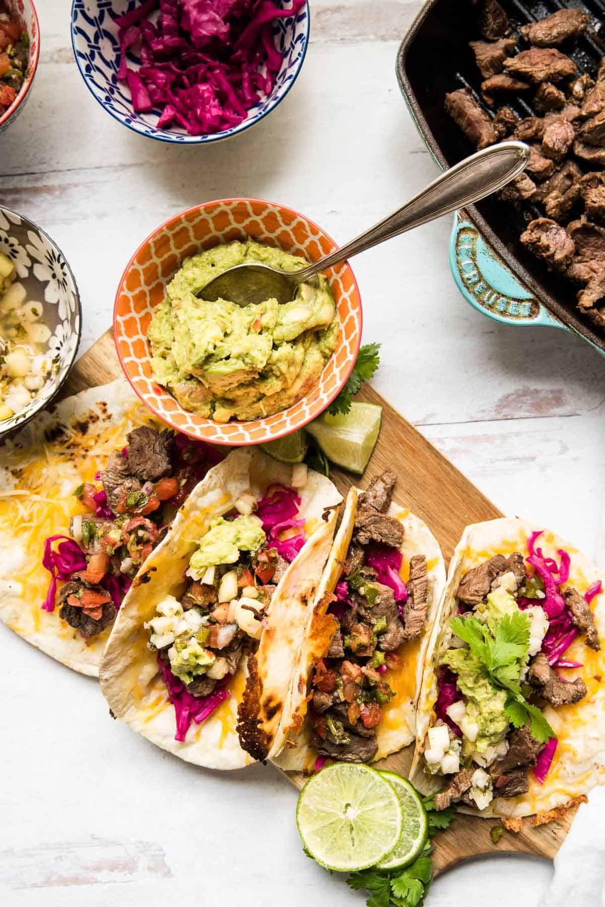four tacos stacked on a wooden board with guac