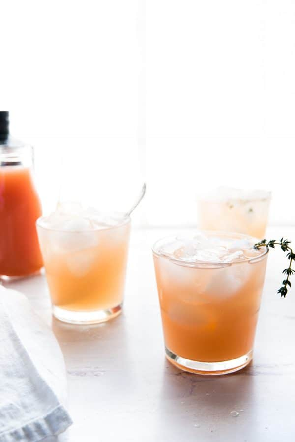 pink cocktail garnished with fresh thyme