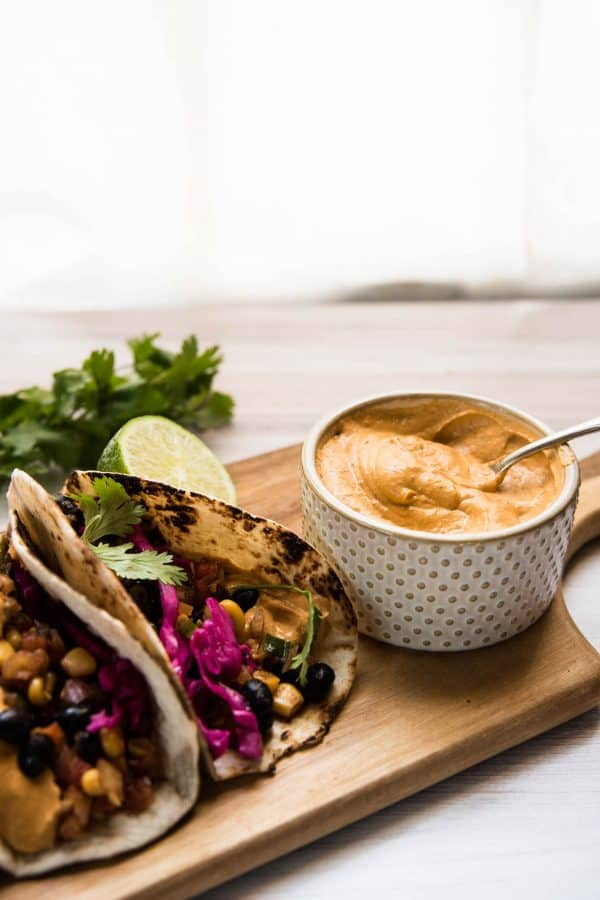 spoon in ramekin of chipotle aioli next to two tacos on a wooden board