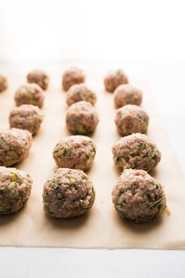 raw meatballs rolled on parchment paper
