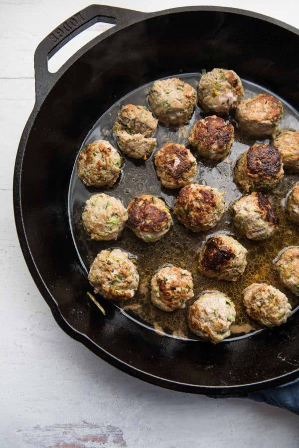 overhead image of zucchini turkey meatballs in a cast iron skillet