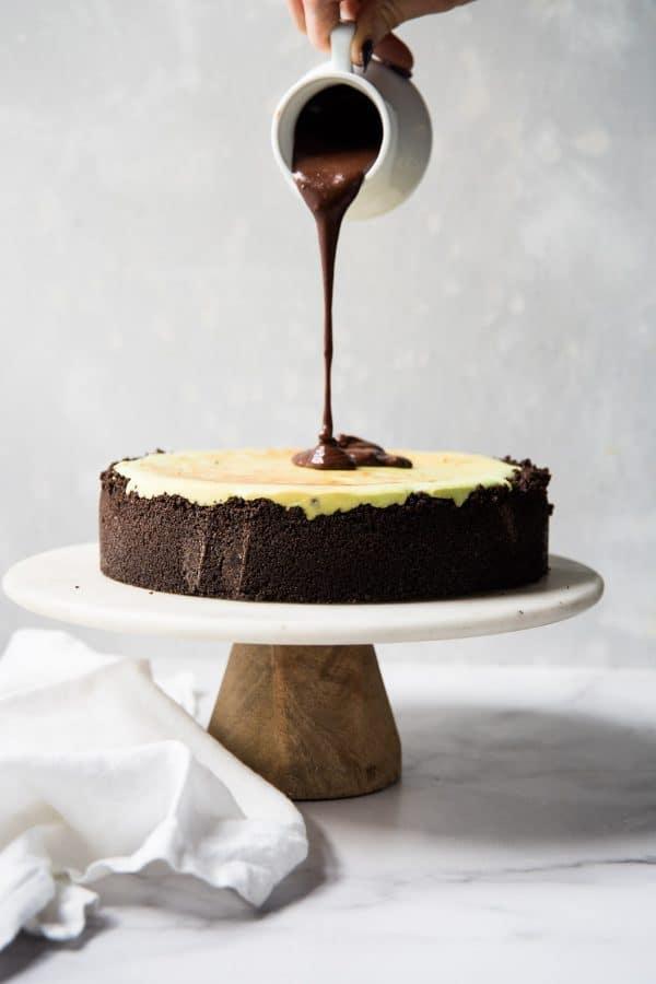 pouring ganache over cheesecake
