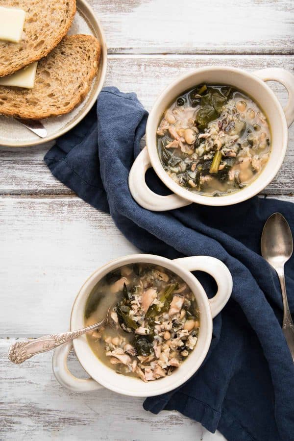 two bowls of soup with buttered bread