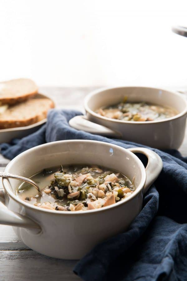 chicken and wild rice soup in bowls with spoon sticking out of them