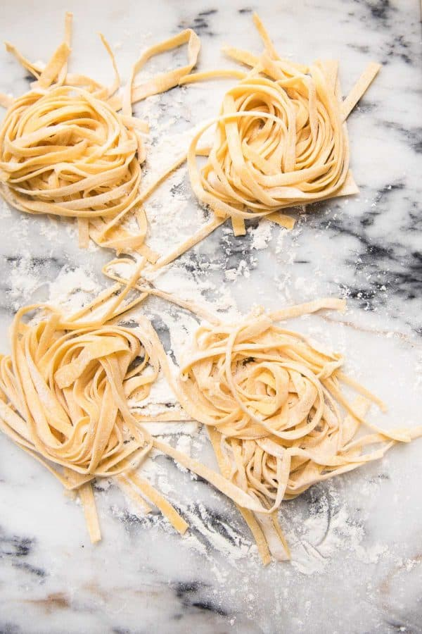 piles of homemade fettucinne dusted with flour