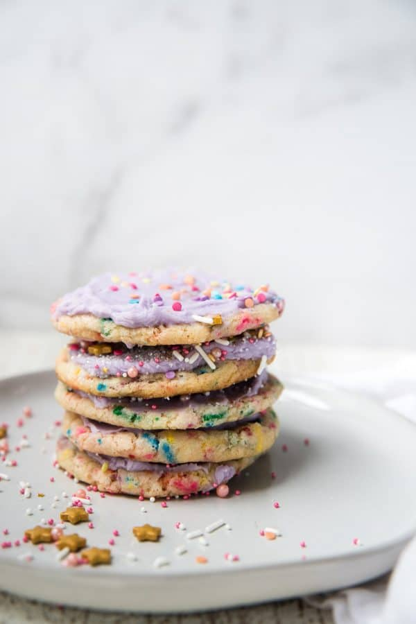 stacked sprinkle cookies frosting with purple frosting