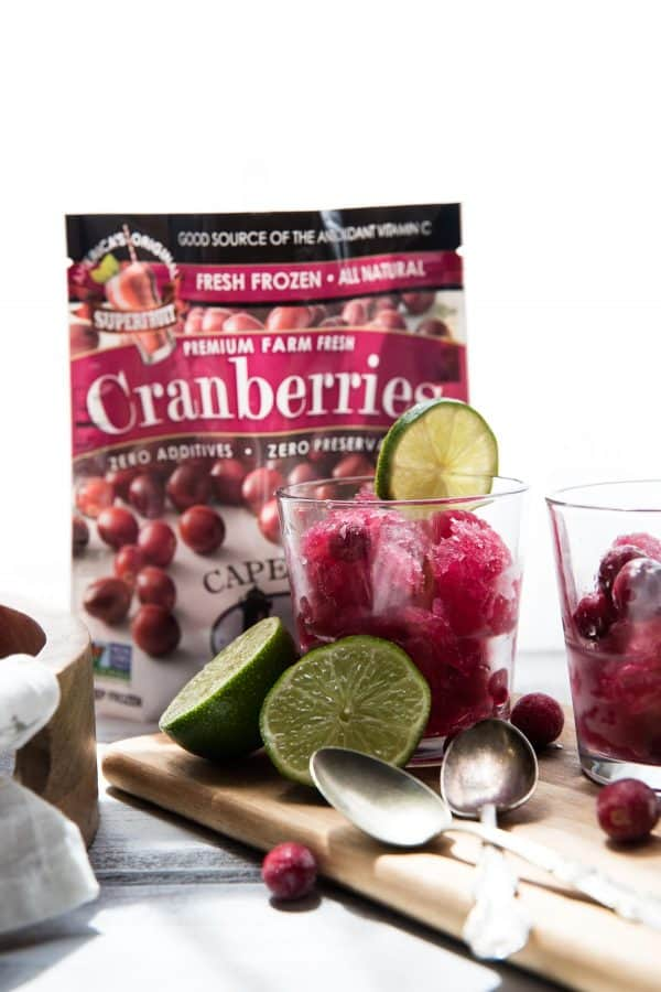 bag of frozen cranberries and glasses filled with frozen cape codder slushies