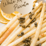 close up of white asparagus with piccata sauce
