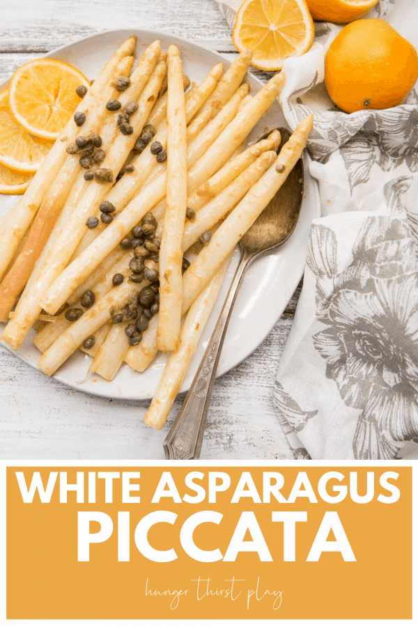 asparagus piccata on a plate with lemon slcies
