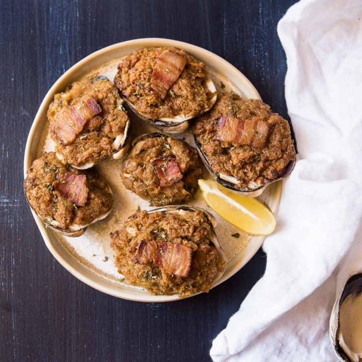 baked stuffed clams on a plate with fresh lemon