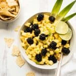 overhead of blackberry pineapple salsa in a serving bowl with chips