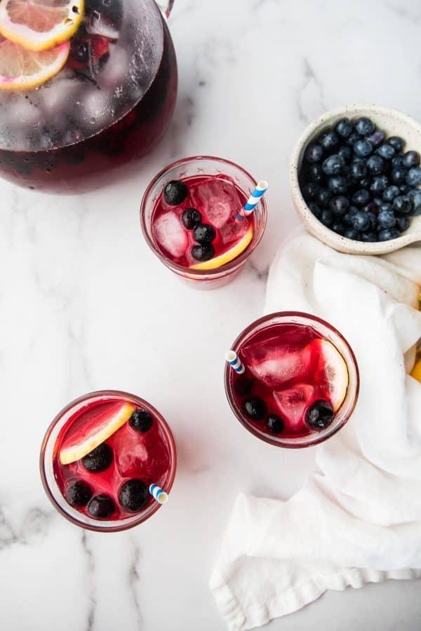 overhead photo of blueberry lemonade in glasses with lemon slices