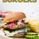burger with toppings on bun with corn and cucumbers on plate