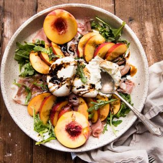 overhead photo of peach burrata salad in a large platter