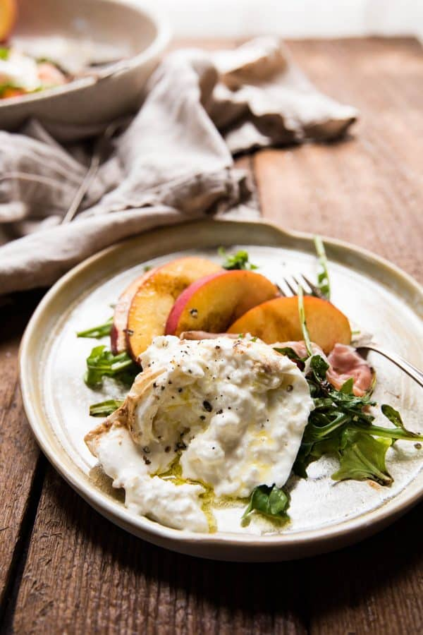 creamy torn burrata on a plate with peaches and arugula