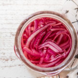 overhead of pickled onions in a mason jar