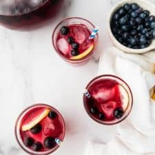 overhead photo of filled glasses and bowl of fruit