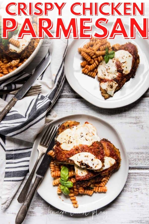 two servings of chicken parmesan over pasta on plates