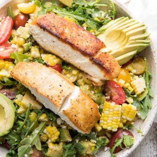close up of pan seared halibut over corn and avocado salad