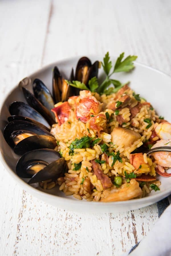 side angle of rice, lobster and mussels in a bowl