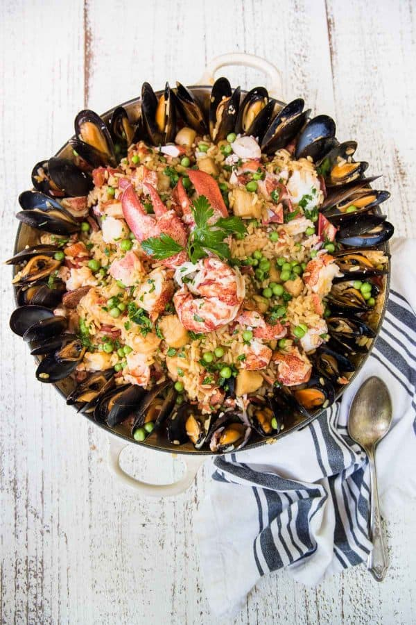 braiser pan with seafood paella surrounded by mussels