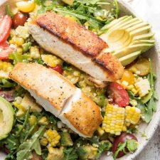 close up of pan seared halibut over corn and avocado salad