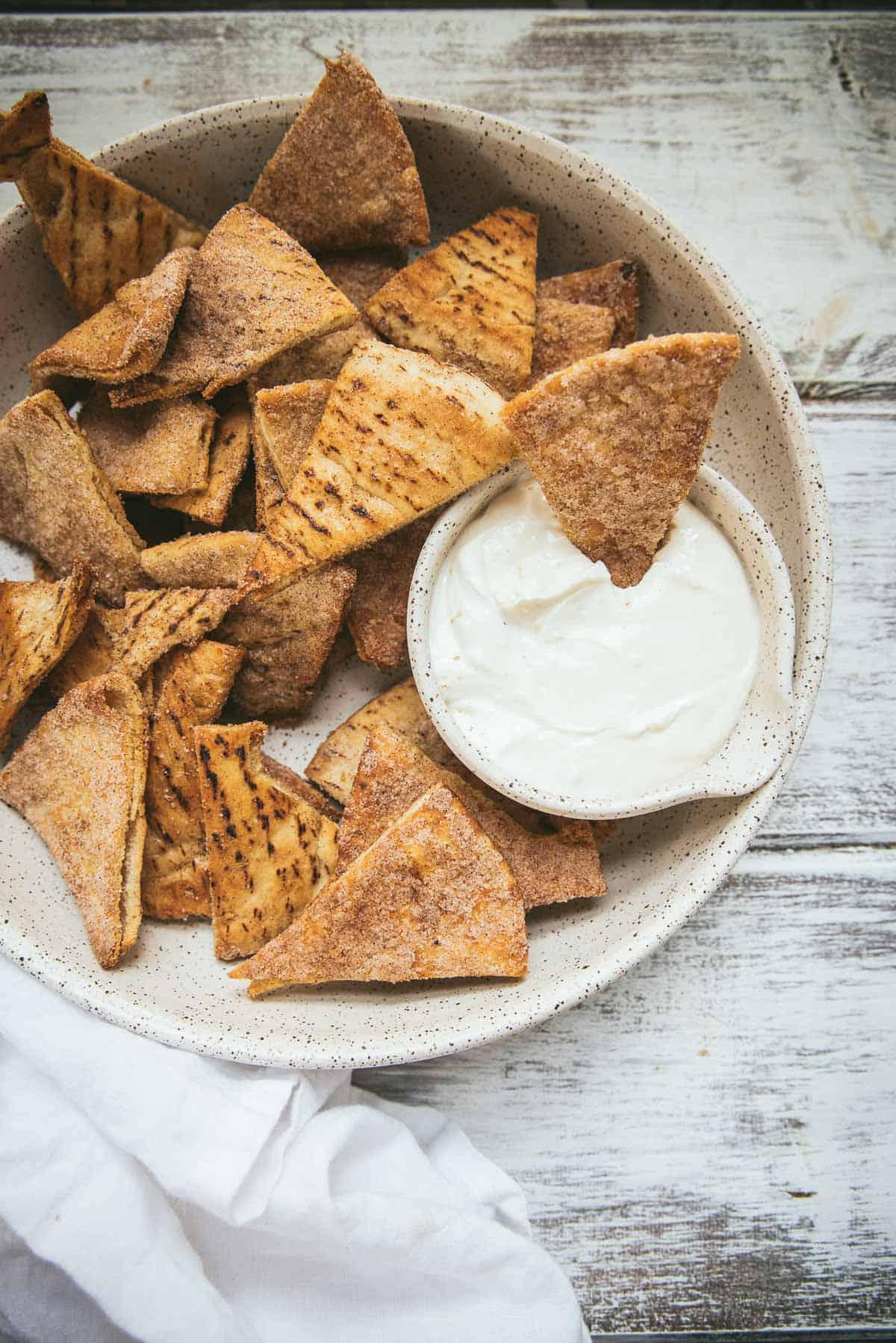 overhead angle of pumpkin spice pita chips in a serving bowl with dip