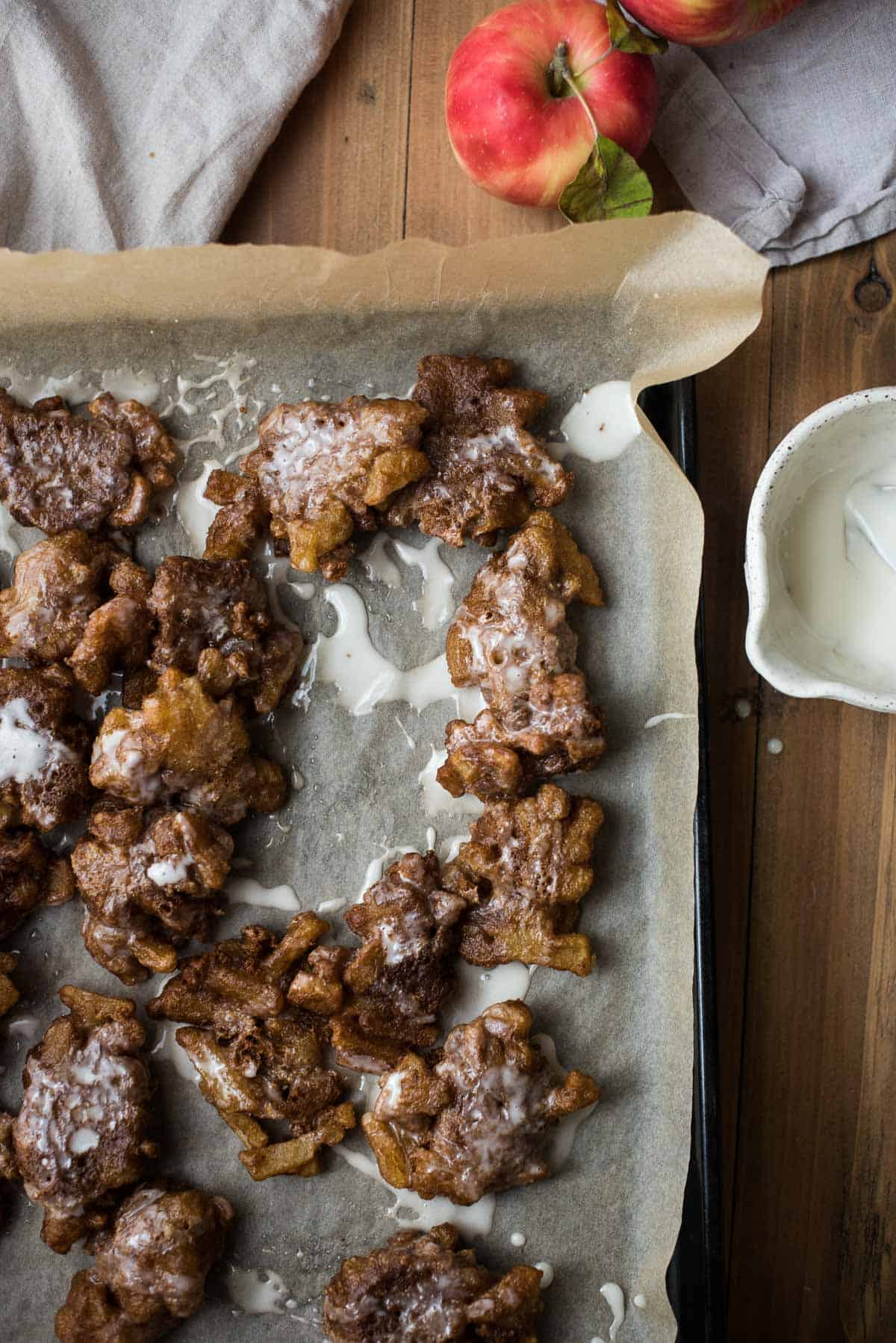 apple fritters on parchment paper with bowl of glaze