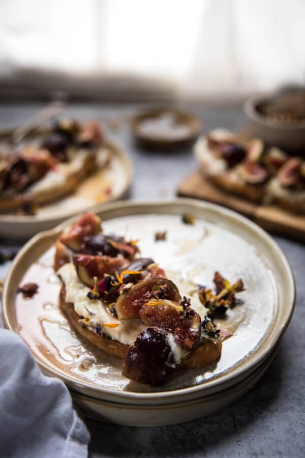close up of ricotta on toast with roasted figs and honey